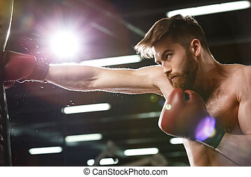 Emotional concentrated young strong sports man boxer