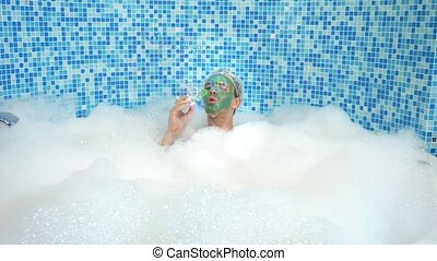 emotional cute man with clay mask in a bathing cap, blowing ...