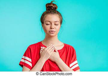 emotional depressed woman holding her palms on the breast.