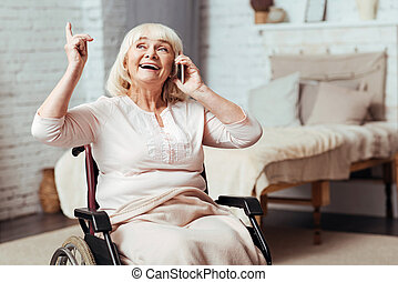 Emotional disabled aged woman talking on cell phone