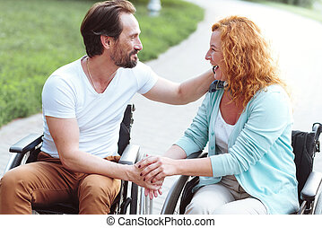 Emotional disabled couple smiling and embracing outdoors
