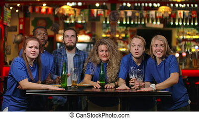 Emotional fans in blue shirts at a beer bar. A multi-ethnic group of African-American people are upset and sad because of the failure of their team. Defeat of your favorite football, volleyball, basketball, hockey team.