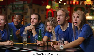 Emotional fans in blue t-shirts at the beer bar....