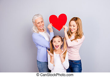 Emotional feeling tenderness gentle warmth concept, Beautiful mum and delightful granny are holding big bright red heart over joy joyful cheerful small girl's head isolated on gray background