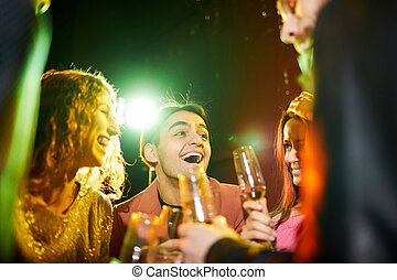 Emotional friends laughing and chatting at party