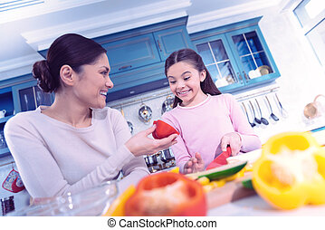 Emotional girl feeling excited while cooking with mother