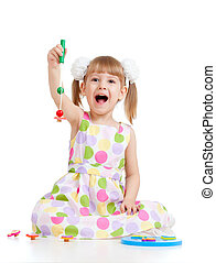 Emotional girl playing with toys, isolated over white