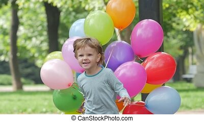 emotional girl runs with multicolored balloons, Slow motion. Close up