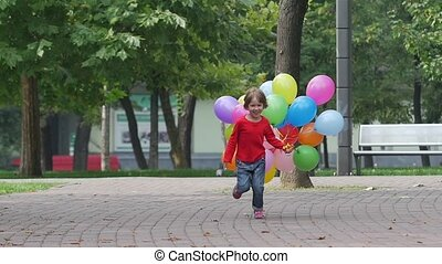 emotional girl runs with multicolored balloons, Slow motion