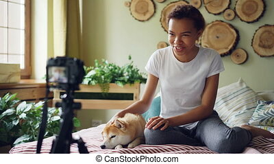 Emotional girl successful blogger is recording video for her online vlog sitting on bed in modern apartment and stroking cute dog lying on bed. Blogging and animals concept.