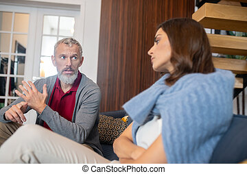 Emotional grey-haired man moralizing his adult daughter