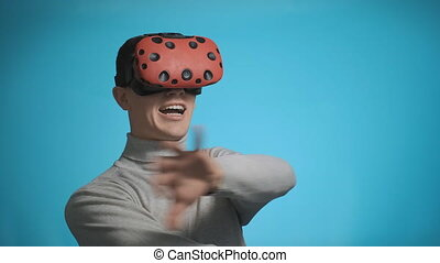 emotional guy with VR glasses clutches head playing - ...