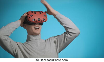 emotional guy with VR glasses clutches head playing on blue...