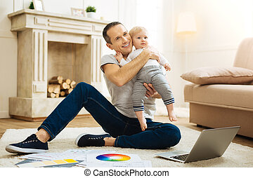 Emotional happy father hugging his child while sitting and working