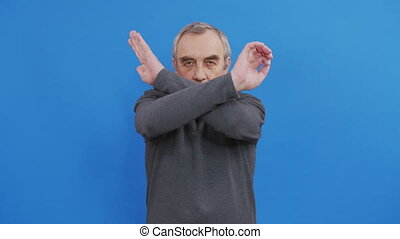 Emotional irritated man crossing hands and saying No, shaking head as denial and rejection, blue studio background