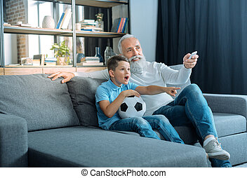 Emotional kid watching tv with grandfather