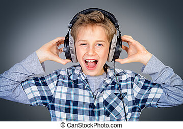 Cheerful teen boy listening to music in headphones and singing a song. Studio shot.