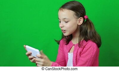 Emotional little girl playing on the smartphone.