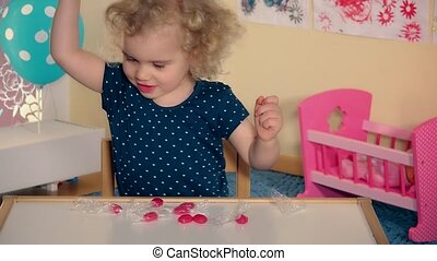 emotional little girl playing with sweet candy on her little...
