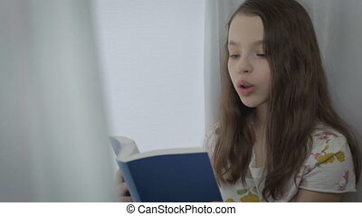 Emotional little girl reading an interesting book by window.