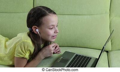 Emotional little girl talking on Skype at laptop. -...