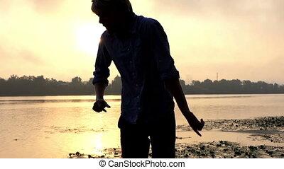 Emotional Man Dances on an Impressive Riverbank at a Splendid Sunset