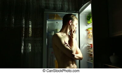 emotional man eating out of the refrigerator at night. happy man