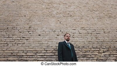 Emotional bearded man in formal clothing gesturing and screaming outdoors. Background of brick wall. Concept of stress at work.