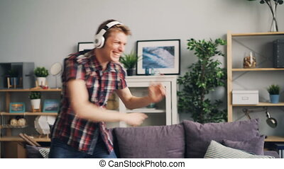 Emotional man melomaniac is listening to rock music through headphones dancing and singing in modern flat having fun. People, modern technology and lifestyle concept.