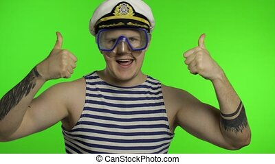 Emotional handsome guy tourist in underwater swimming goggles mask wear striped sailor shirt vest dances and celebrates. Chroma key background. Muscular sailor man. Concept of tourism, sea resorts
