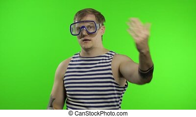 Emotional handsome guy tourist in underwater swimming goggles mask wear striped sailor shirt vest. Chroma key background. Muscular sailor man show thumbs up. Concept of tourism, sea resorts