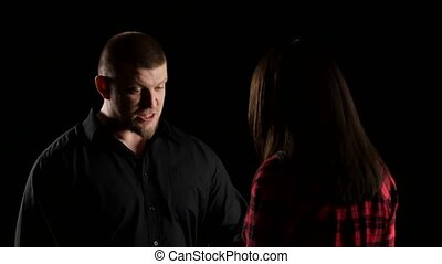 Emotional man with woman says irritably on black background. Close-up