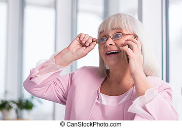 Emotional mature woman talking to someone on the phone