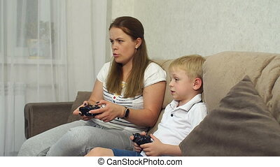 Emotional mom and son play video games sitting at home on the couch.