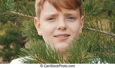 Emotional portrait of a teenage boy who stands near a fir...