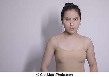emotional portrait of attractive brunette, actress in a beige undershirt - bodysuit on white background. space for text