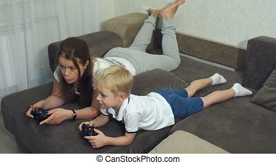 Emotional portrait of mom and son at home on the couch, they play a video game.