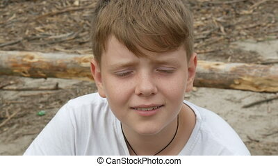 Emotional portrait of red-haired teenager boy with blue eyes...