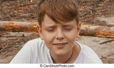 Emotional portrait of red-haired teenager boy with blue eyes and freckles that looks into the camera