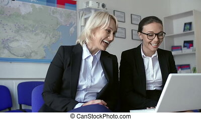 Emotional Release - Two business women laughing at something...
