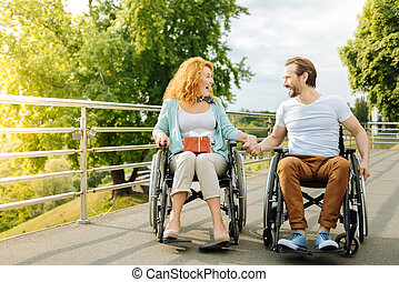 Emotional senior couple resting outdoors in the wheelchairs
