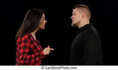 Emotional showdown between man and woman. Isolated on black background. Close up