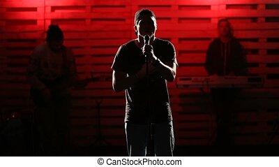 Emotional singer singing on illuminated stage
