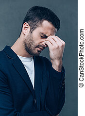 Emotional stress. Side view of frustrated young man touching his forehead while standing against grey background