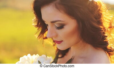 Emotional touched beautiful brunette bride in white dress in wreath with make-up close-up shot in slow motion  close up