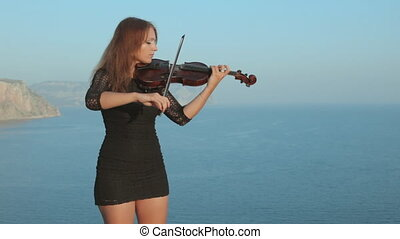 Emotional violinist playing while standing on ?rimean...