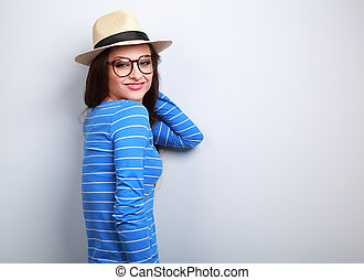 Emotional woman in straw hat and eye glasses looking happy on blue background