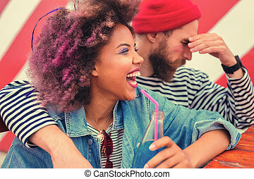 Emotional woman laughing and her boyfriend having headache after party