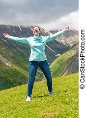 Emotional woman with open arms in the mountains enjoys freedom