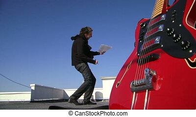Singer emotionally wrote a new song. Front of the camera a red electric guitar.